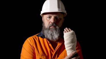 A male worker with a hand injury, on a black background with copy space.